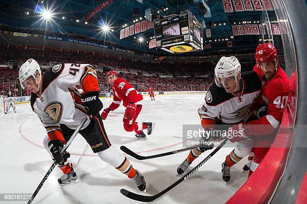 Josh Manson of the Anaheim Ducks takes the puck off the boards as teammate Jakob Silfverberg ties up Henrik Zetterberg of the Detroit Red Wings...