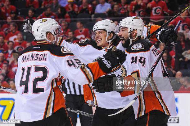 Josh Manson Rickard Rakell and Nate Thompson of the Anaheim Ducks celebrate the winning goal of their teammate Corey Perry against the Calgary Flames...