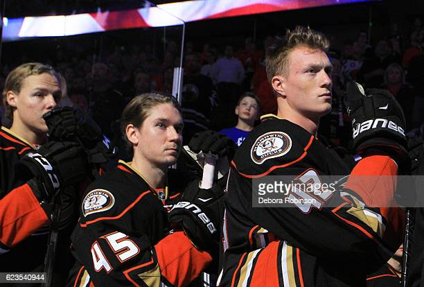 Josh Manson Sami Vatanen and Hampus Lindholm of the Anaheim Ducks listen to the national anthem prior to the game against the Edmonton Oilers on...