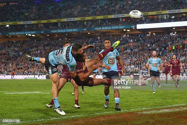 Josh Mansour of the Blues and Justin O'Neill of the Maroons compete for the ball from a kick during game one of the State Of Origin series between...
