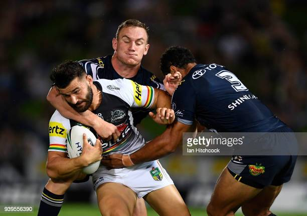 Josh Mansour of the Panthers is tackled by Coen Hess and Justin O'Neil of the Cowboys during the round four NRL match between the North Queensland...