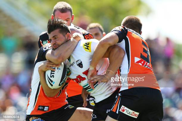 Josh Mansour of the Panthers is tackled by the Tigers defence during the round two NRL match between the Wests Tigers and the Penrith Panthers at...