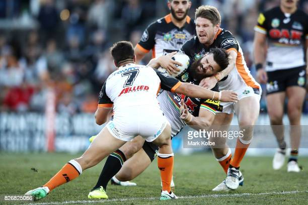 Josh Mansour of the Panthers is tackled during the round 22 NRL match between the Penrith Panthers and the Wests Tigers at Pepper Stadium on August 6...