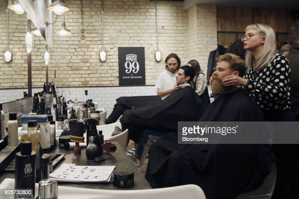 Josh Mario John, model and lifestyle blogger, second right, has his beard groomed during a launch event for House 99, a grooming brand for men...