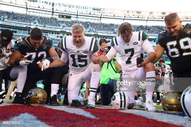 Josh McCown and Chandler Catanzaro of the New York Jets pray with Josh Wells and Tyler Shatley of the Jacksonville Jaguars aftertheir game at MetLife...