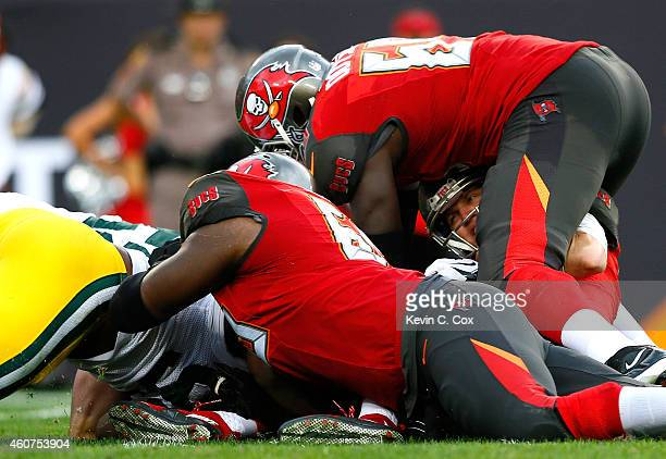 Josh McCown of the Tampa Bay Buccaneers is sacked by Clay Matthews and Datone Jones of the Green Bay Packers at Raymond James Stadium on December 21...