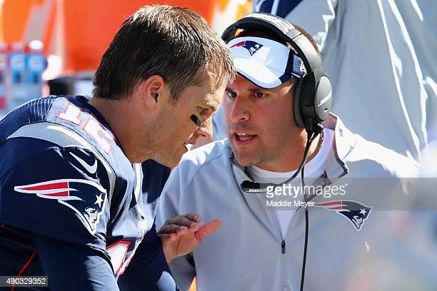 Josh McDaniels offensive coordinator for the New England Patriots congratulates Tom Brady of the New England Patriots after his 400th career...