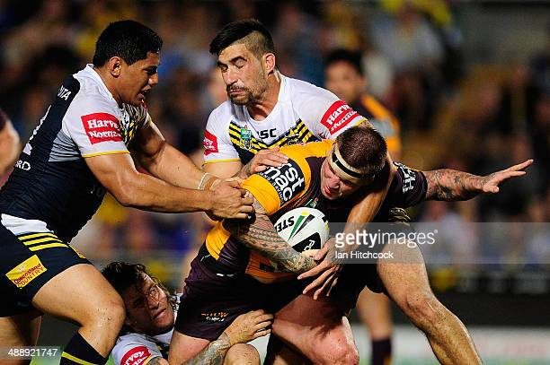 Josh McGuire of the Broncos is tackled by James Tamou and Jason Taumalolo of the Cowboys during the round nine NRL match between the North Queensland...