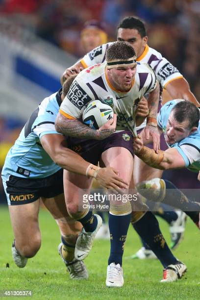 Josh McGuire of the Broncos is tackled during the round 16 NRL match between the Brisbane Broncos and the Cronulla Sharks at Suncorp Stadium on June...