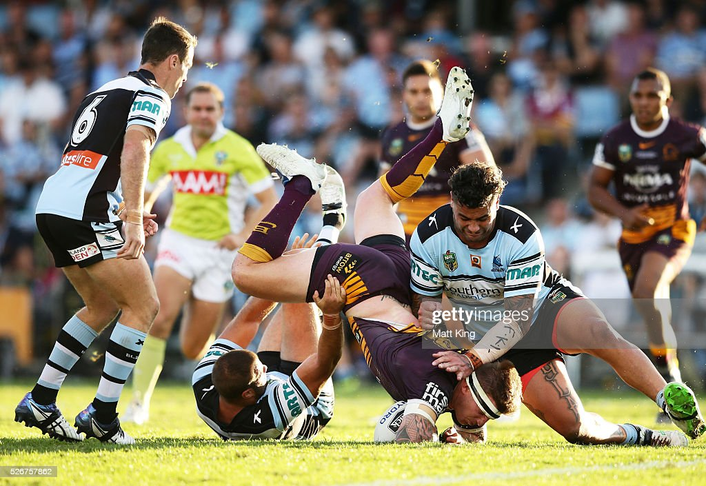 Josh McGuire of the Broncos is tackled heavily during the round nine NRL match between the Cronulla Sharks and the Brisbane Broncos at Southern Cross Group Stadium on May 1, 2016 in Sydney, Australia.