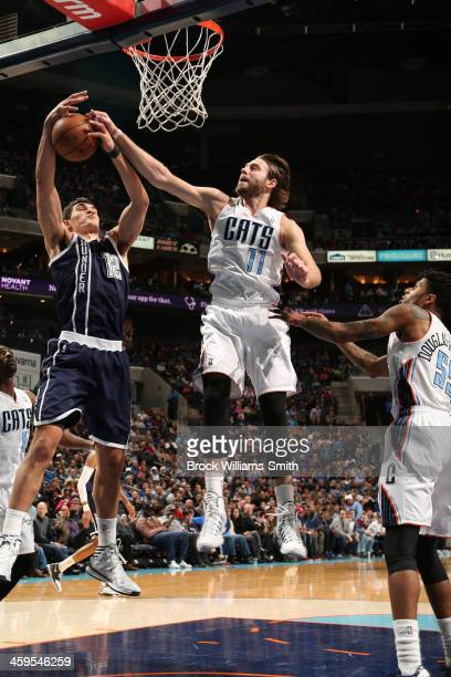 Josh McRoberts of the Charlotte Bobcats blocks a shot against Steven Adams of the Oklahoma City Thunder during the game at the Time Warner Cable...