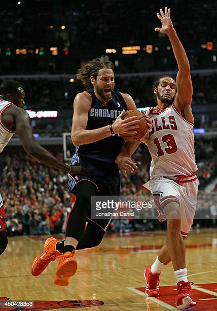 Josh McRoberts of the Charlotte Bobcats drives between Loul Deng and Joakim Noah of the Chicago Bulls at the United Center on November 18 2013 in...