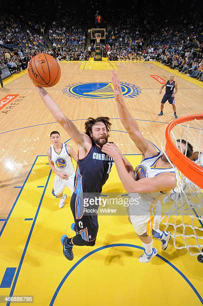 Josh McRoberts of the Charlotte Bobcats dunks against Andrew Bogut of the Golden State Warriors on February 4 2014 at Oracle Arena in Oakland...