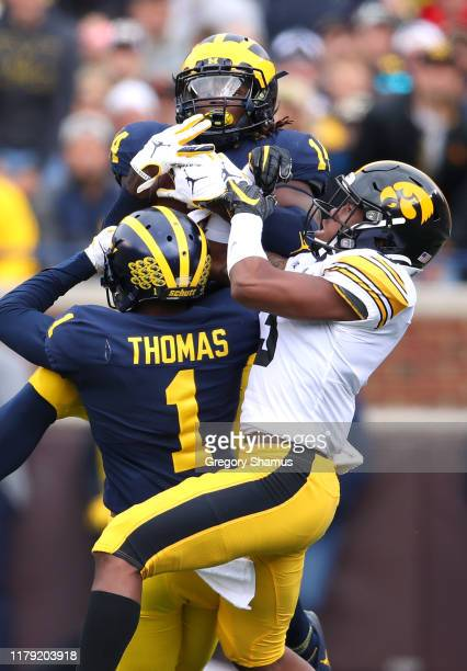 Josh Metellus of the Michigan Wolverines makes a first quarter interception next to Tyrone Tracy Jr #3 of the Iowa Hawkeyes and his teammate Ambry...