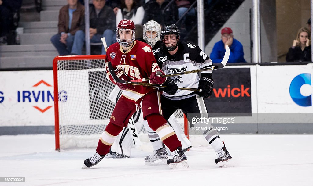 Josh Monk #27 of the Providence College Friars checks Blake Hillman #25 of the Denver Pioneers during NCAA hockey at the Schneider Arena on December 30, 2016 in Providence, Rhode Island. The game ended in a 2-2 tie.