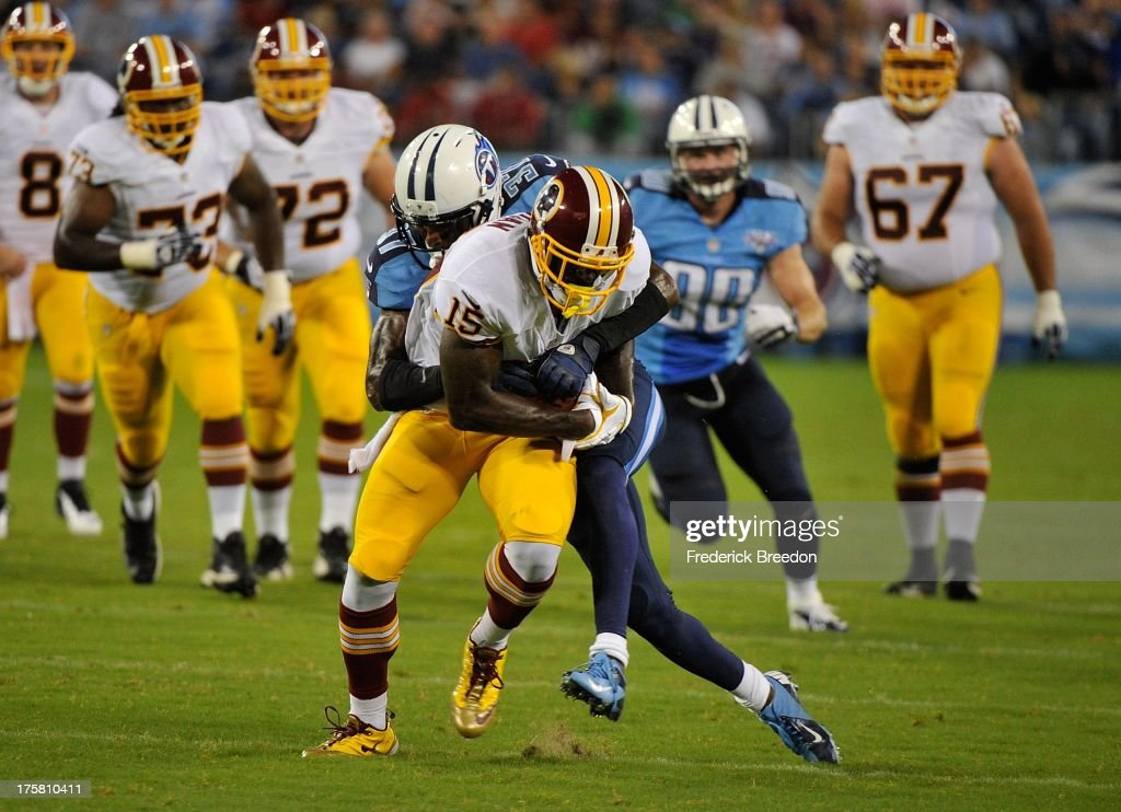 Josh Morgan #15 of the Washington Redskins is tackled from behind by Tommie Campbell #37 of the Tennessee Titans during a pre-season game at LP Field on August 8, 2013 in Nashville, Tennessee.