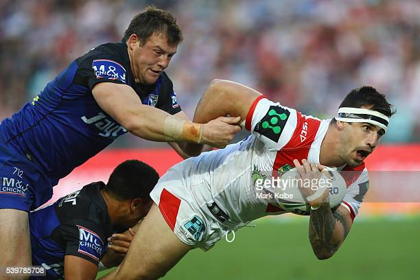 Josh Morris and Moses Mbye of the Bulldogs tackle Jacob Marketo of the Dragons during the round 14 NRL match between the St George Illawarra Dragons...