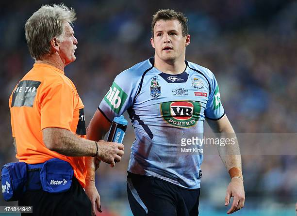 Josh Morris of the Blues is assisted by a trainer during game one of the State of Origin series between the New South Wales Blues and the Queensland...