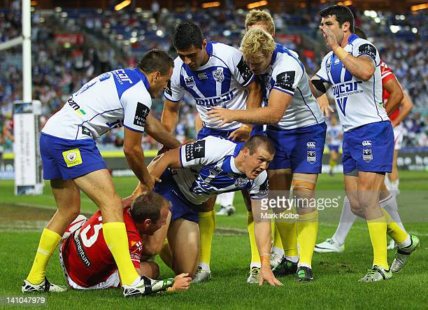 Josh Morris of the Bulldogs is congratulated by his team after scoring a try during the round two NRL match between the Canterbury Bulldogs and the...