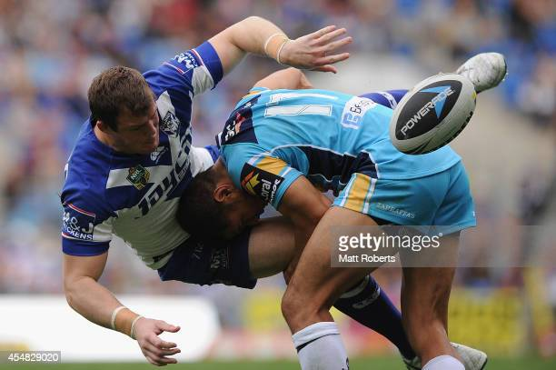 Josh Morris of the Bulldogs is tackled by David Mead of the Titans during the round 26 NRL match between the Gold Coast Titans and the Canterbury...
