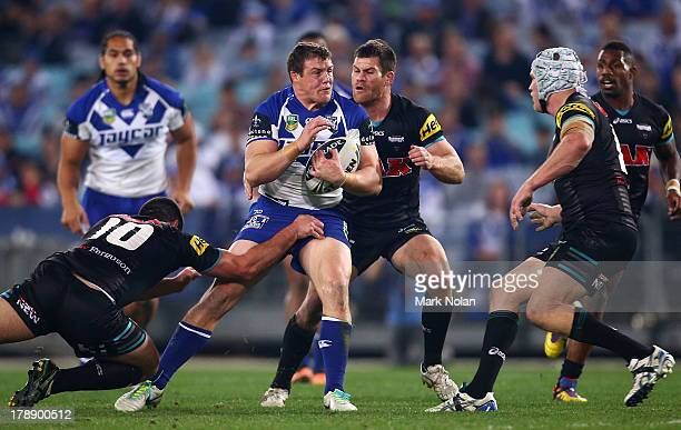 Josh Morris of the Bulldogs is tackled during the round 25 NRL match between the Canterbury Bulldogs and the Penrith Panthers at ANZ Stadium on...