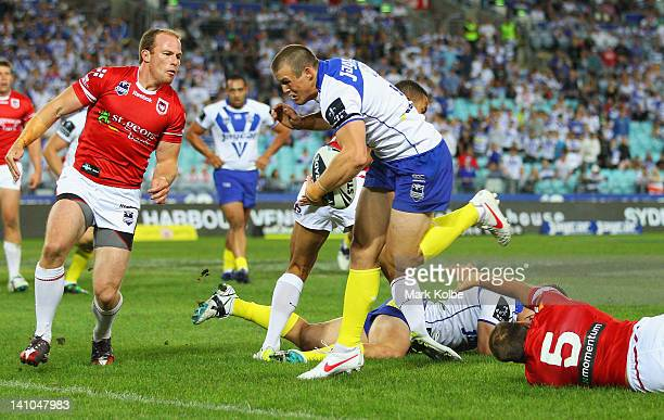 Josh Morris of the Bulldogs makes a break on his way to scoring a try during the round two NRL match between the Canterbury Bulldogs and the St...