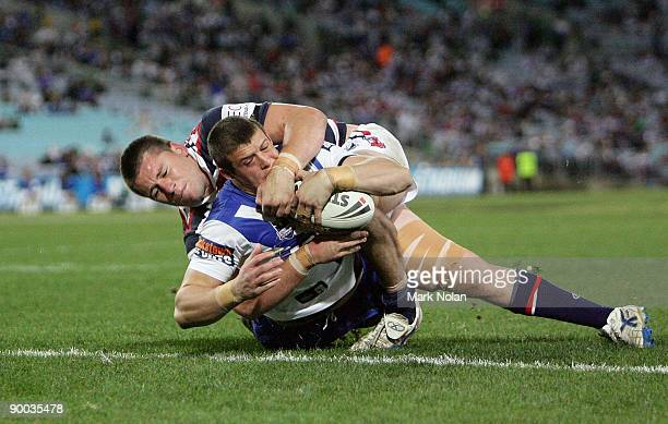 Josh Morris of the Bulldogs scores as Shaun Kenny-Dowall of the Roosters tackles during the round 24 NRL match between the Bulldogs and the Sydney...