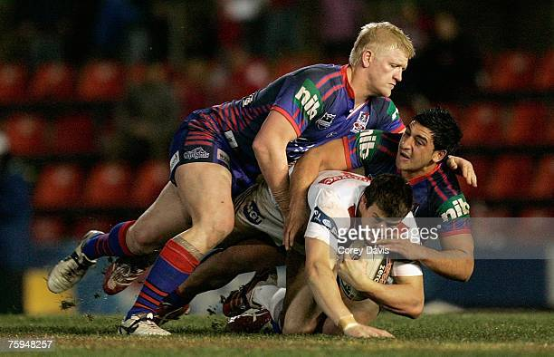 Josh Morris of the Dragons is tackled by Mitchell Sargent and Marvin Karawana of the Knights during the round 21 NRL match between the Newcastle...