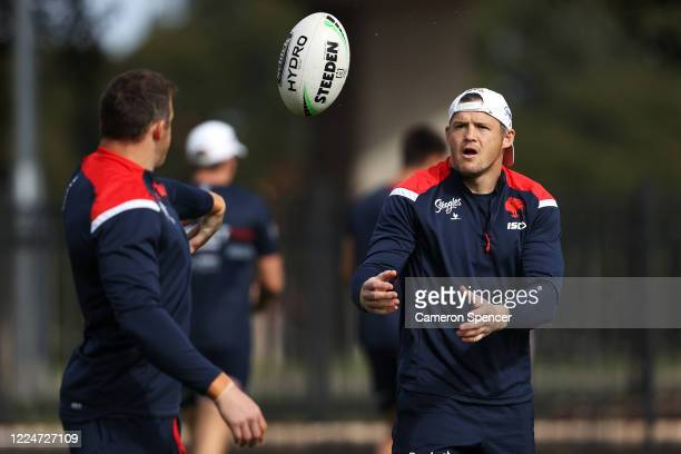 Josh Morris of the Roosters passes to team mate Brett Morris during a Sydney Roosters NRL training session at Kippax Lake Field on May 14, 2020 in...