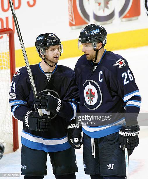 Josh Morrissey and Blake Wheeler of the Winnipeg Jets discuss strategy during a second period stoppage in play against the Montreal Canadiens at the...