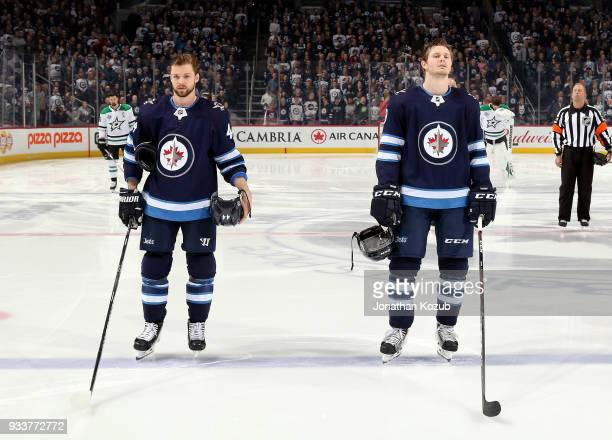 Josh Morrissey and Jacob Trouba of the Winnipeg Jets stand on the ice during the singing of the National anthems prior to puck drop against the...