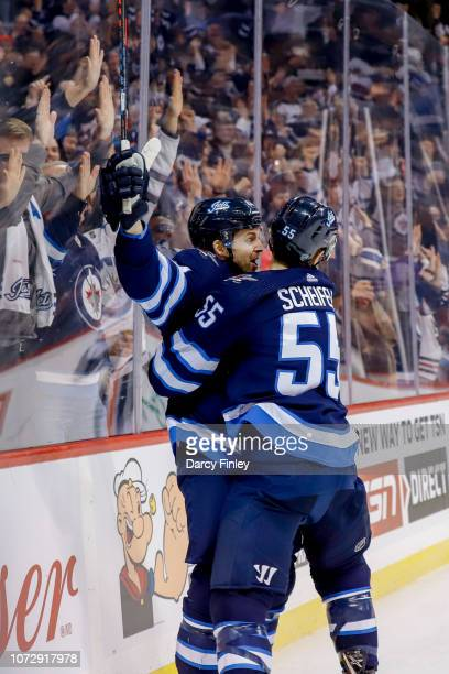 Josh Morrissey and Mark Scheifele of the Winnipeg Jets celebrate an overtime goal against the Edmonton Oilers at the Bell MTS Place on December 13...