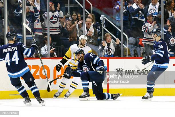 Josh Morrissey and Mark Scheifele of the Winnipeg Jets join Blake Wheeler as he celebrates his first period hat trick against the Pittsburgh Penguins...