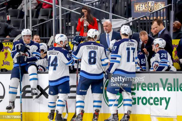 Josh Morrissey Jacob Trouba and Adam Lowry of the Winnipeg Jets gather at the bench while Head Coach Paul Maurice discusses strategy with Patrik...