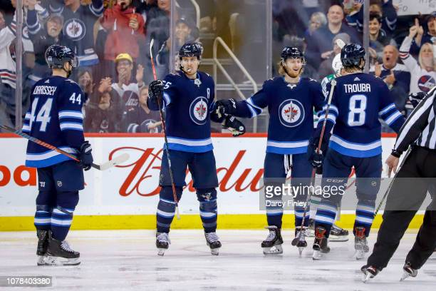 Josh Morrissey Mark Scheifele Kyle Connor and Jacob Trouba of the Winnipeg Jets celebrate a third period goal against the Dallas Stars at the Bell...