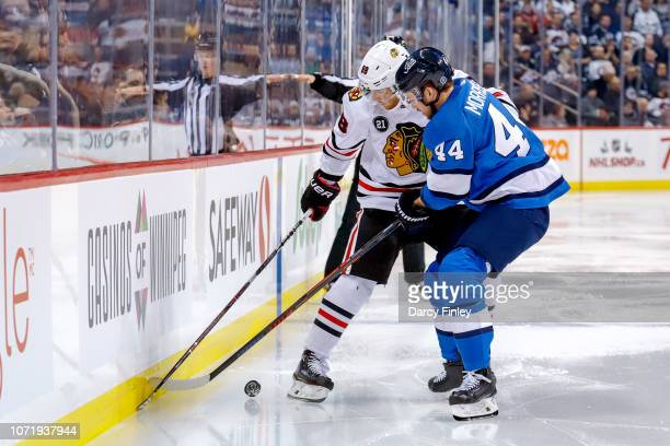 Josh Morrissey of the Winnipeg Jets and Patrick Kane of the Chicago Blackhawks battle for the puck along the boards during third period action at the...