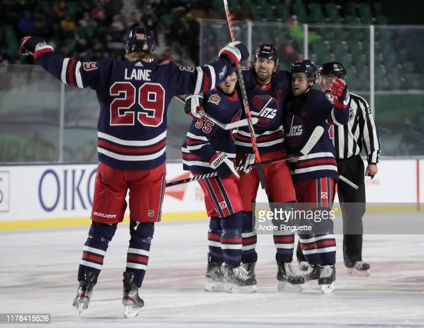 Josh Morrissey of the Winnipeg Jets celebrates with teammates Mark Scheifele, Blake Wheeler and Patrik Laine after scoring a third period goal on the...
