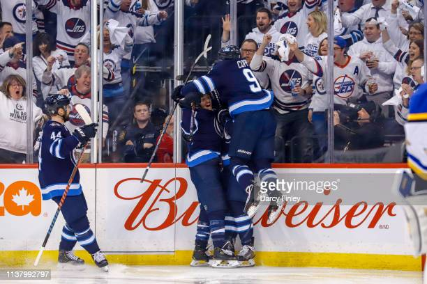 Josh Morrissey of the Winnipeg Jets joins teammates Brandon Tanev Adam Lowry and Andrew Copp as they celebrate a first period goal against the St...
