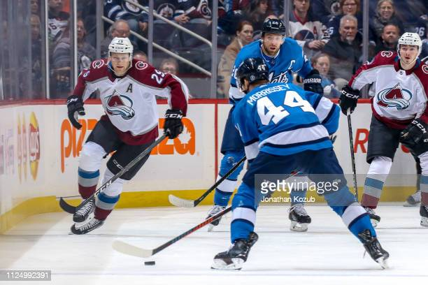 Josh Morrissey of the Winnipeg Jets plays the puck at the point as Nathan MacKinnon of the Colorado Avalanche rushes to defend during first period...