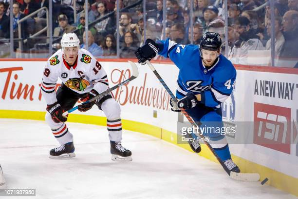 Josh Morrissey of the Winnipeg Jets plays the puck away from Jonathan Toews of the Chicago Blackhawks during third period action at the Bell MTS...