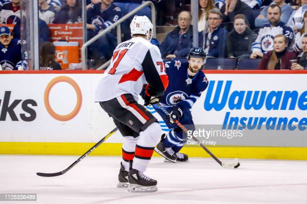 Josh Morrissey of the Winnipeg Jets plays the puck down the ice as Chris Tierney of the Ottawa Senators defends during the overtime period at the...