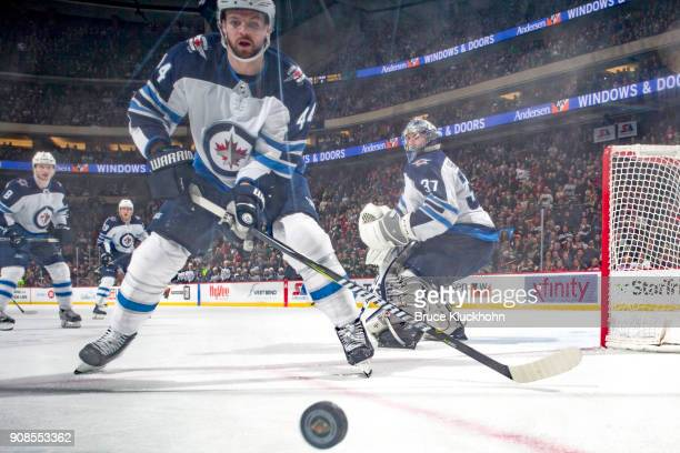 Josh Morrissey skates to the puck while his Winnipeg Jets teammate Connor Hellebuyck defends against the Minnesota Wild during the game at the Xcel...