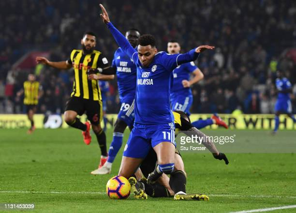Josh Murphy of Cardiff City is challenged by Daryl Janmaat of Watford in the penalty area during the Premier League match between Cardiff City and...