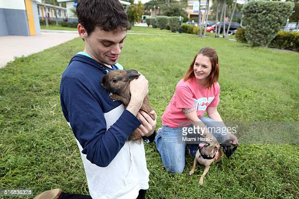 Josh Nackenson with his pet therapy rabbit Peanut and Crystal Jacques with her pet therapy dog Oliver meet in a grassy area outside of the Arch Creek...