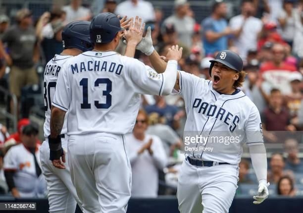 Josh Naylor of the San Diego Padres is congratulated by Eric Hosmer and Manny Machado after hitting a three-run home run during the third inning of a...