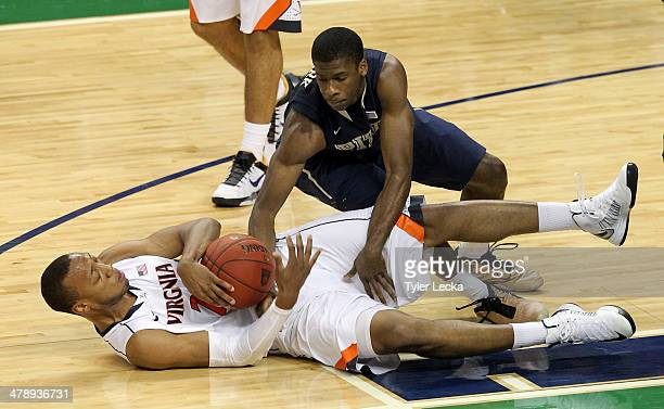 Josh Newkirk of the Pittsburgh Panthers and Akil Mitchell of the Virginia Cavaliers battle for a loose ball during the semifinals of the 2014 Men's...