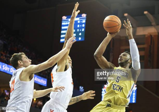 Josh Okogie of the Georgia Tech Yellow Jackets shoots over Devon Hall and Ty Jerome of the Virginia Cavaliers in the first half during a game at John...