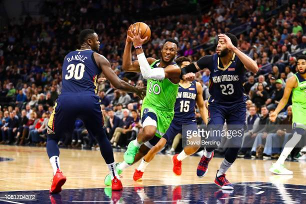 Josh Okogie of the Minnesota Timberwolves runs with the ball while Julius Randle and Anthony Davis of the New Orleans Pelicans defend in the third...