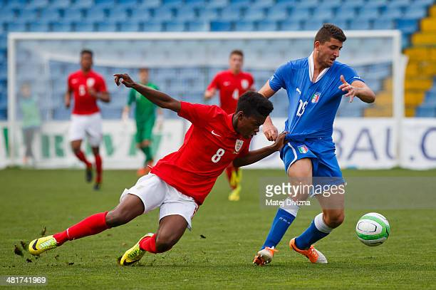 Josh Onomah of England competes for the ball with Mauro Coppolaro of Italy during the UEFA U17 Championship Qualifier Elite Round match between Italy...
