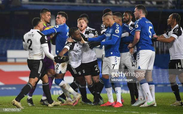 Josh Onomah of Fulham is held back by Harrison Reed as he clashes with Richarlison and Michael Keane of Everton during the Premier League match...